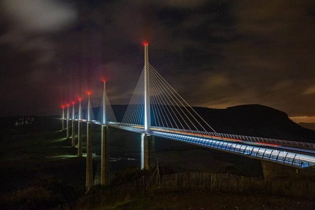 You're looking at the tallest bridge in Europe and one of the tallest in the world.  Opened in 2004, the Millau Viaduct rises 336.4 metres above the valley of the River Tarn in France.  It's quite the sight!  #MillauViaduct #visitfrance #bridge #bridgesofinstagram #BridgePorn #engineering #night #vanlifeeurope #homeiswhereyouparkit #theroadismyhome #travelphotography #travelbloggers